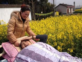 妻子推着病床带瘫痪丈夫看油菜花